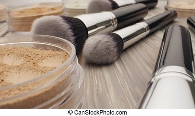 Brush for make-up with powder on a wooden table