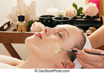 Cosmetics - applying facial mask - Woman having a mask or...