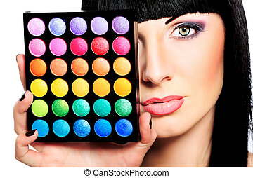 cosmetics - Beautiful young woman holding eye shadow palette...