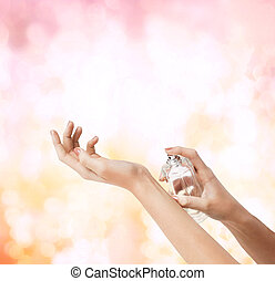 woman hands spraying perfume - cosmetics, body parts and...