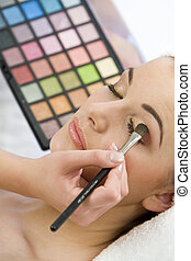 Cosmetics - A beautiful young woman having the final touches...