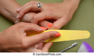 Cosmetologist cleans nails, nail file.
