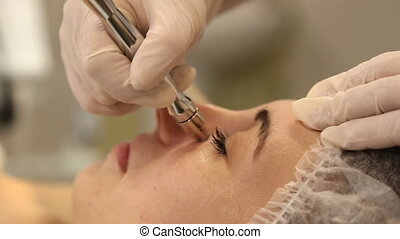 cosmetologist doing facial massage - Beautician doing a...