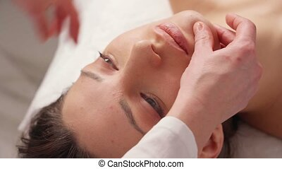cosmetologist makes a buccal massage of the patient's facial muscles