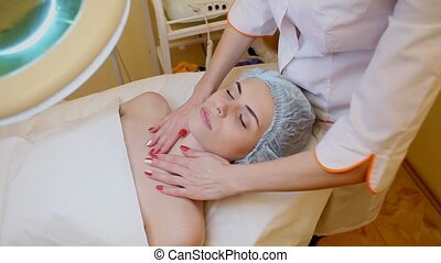 cosmetologist makes a woman face and neck massage Spa