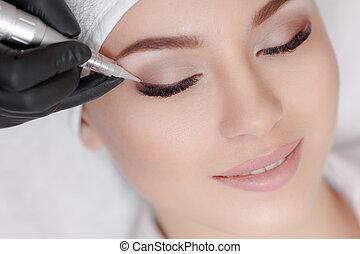 Cosmetologist making permanent make up at beauty salon -...