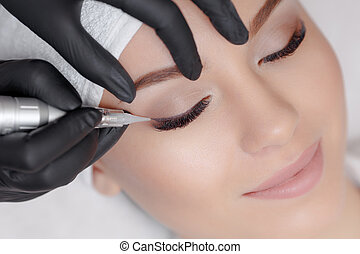 Cosmetologist making permanent makeup, close up. Tattooist...