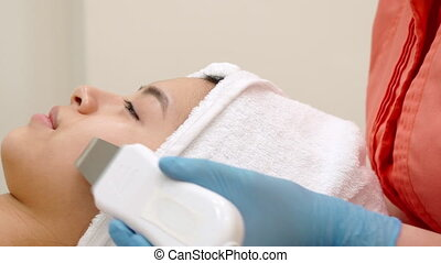 Cosmetologist peels woman's chin