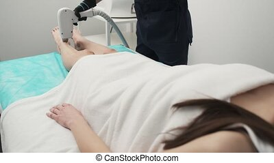 Cosmetologist performs laser hair removal on the client's feet in a beauty studio.