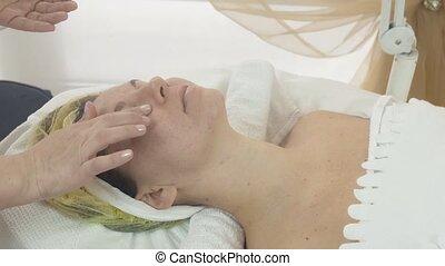 Cosmetologist smear bit moisturizing oil on woman face in...