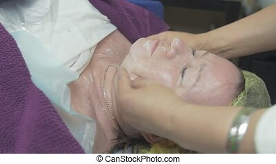 Cosmetologist smear moisturizing cream on thick woman face...