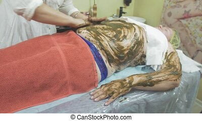 Cosmetologist smears seaweed mixture on fat woman stomach,...