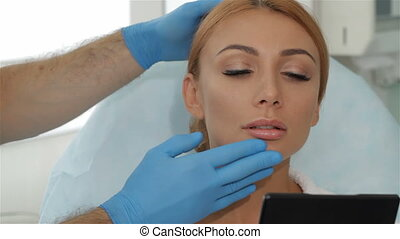 Cosmetologist stretches the skin over the brow of the client