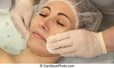 cosmetologist woman wipes her face