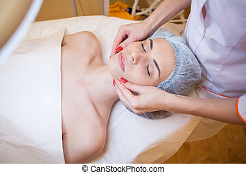 Cosmetology doctor makes woman treatments facial massage