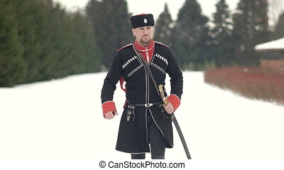 Cossack with daggers walking along the winter landscape. A...