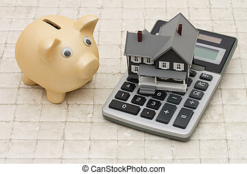 A gray house, piggy bank and calculator on stone background...