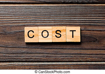 costs word written on wood block. costs text on wooden table for your desing, Top view concept