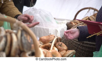Costumer buying ring shaped bread rolls seasoned with poppy...