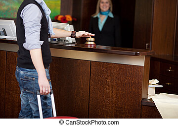 costumer ringing bell at hotel counter - male costumer with...