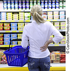 blond woman shopping in the supermarket choosing a dairy product