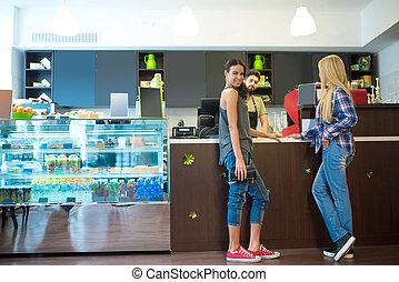 Costumers in a coffee shop - Two beautiful young woman...