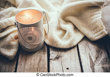 Cosy and soft winter background, knitted sweater and candles...
