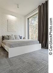 Cosy bedroom with bed huge window
