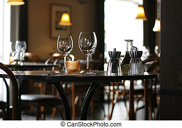 Interior of a cozy restaurant focusing on a ready table for two