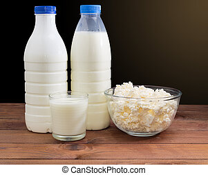 Cottage cheese in bowl, other dairy products on rustic table