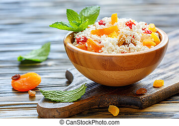 Cottage cheese with dried apricots and raisins in a wooden bowl.