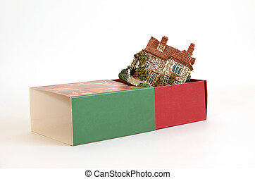 Cottage in a gift box on white background