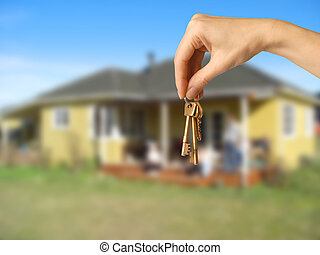 cottage keys - female hand holding keys in front of a...