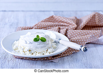 cottage with sour cream and on the plate