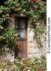 cottage with roses around door