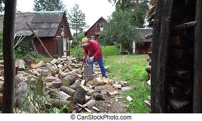 cottager split hard log in country woodshed in summertime....