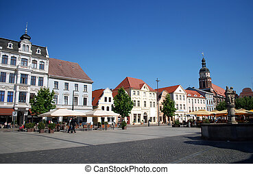 cottbus alttmarkt, germany, with historic well and cafe