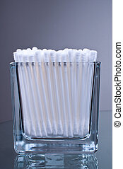 Cotton buds in glass on a glass table
