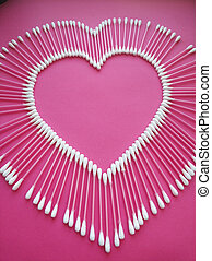 cotton buds laid out in the shape of a heart on a pink background