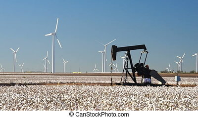 A Pump Jack endlessly fracking as wind turbines whirl in a harvest ready cotton field