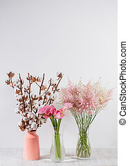 cotton flowers in a vase on wooden background