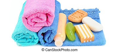 Cotton towels, cosmetic soap and shampoo isolated on white. Wide photo.