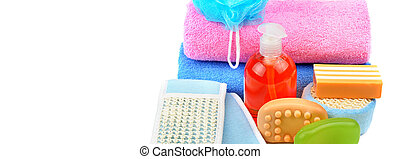 Cotton towels, cosmetic soap, sponge and shampoo isolated on white background. Wide photo.