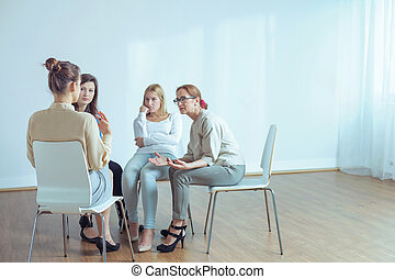 Couch talking with young women during training in the office