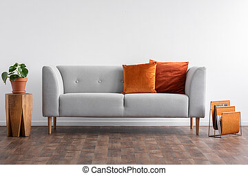 Couch with pillows between wooden table with plant in pot and newspaper organizer, real photo with copy space on the empty white wall