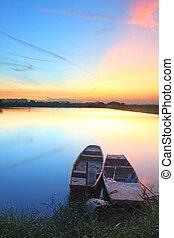 coucher soleil, à, isolé, bateaux, dans, eau, corps