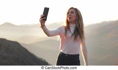 coucher soleil, apprécier, vêtements, rigolote, vue, beau, téléphoner femme, dessus blanc, séjour, voyage, montagne, nuageux, aventure, rocher, jeune, heureux, selfie