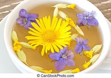 Cough tea with blossoms of coltsfoot, violets and cowslip in a white cup
