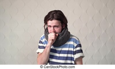 Young guy cannot stop coughing, indoor shot of an ill boy with a warm knitted scarf around the neck
