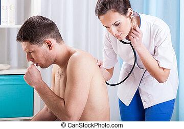 Coughing man having examination - Horizontal view of ...